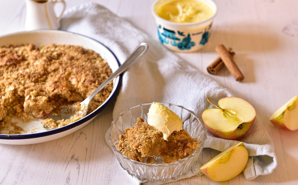 Apple Crumble with Clotted cream served in a glass bowl